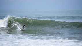 Eine Stellung herauf den Paddelinternatsschüler, der eine Welle surft Lizenzfreie Stockfotos