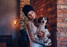 Eine stilvolle tattoed blonde Frau im T-Shirt und in den Jeans hält einen netten Hund Stockfotos