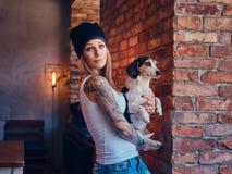 Eine stilvolle tattoed blonde Frau im T-Shirt und in den Jeans hält einen netten Hund Lizenzfreies Stockbild