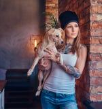 Eine stilvolle tattoed blonde Frau im T-Shirt und in den Jeans hält einen netten Hund Stockfotografie