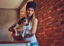 Eine stilvolle tattoed blonde Frau im T-Shirt und in den Jeans hält einen netten Hund Lizenzfreies Stockfoto