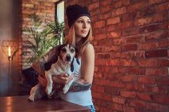 Eine stilvolle tattoed blonde Frau im T-Shirt und in den Jeans hält einen netten Hund Stockbilder