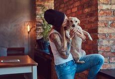 Eine stilvolle tattoed blonde Frau im T-Shirt und in den Jeans hält einen netten Hund Lizenzfreie Stockfotografie