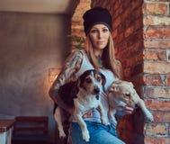 Eine stilvolle tattoed blonde Frau im T-Shirt und in den Jeans hält zwei nette Hunde Lizenzfreie Stockfotos
