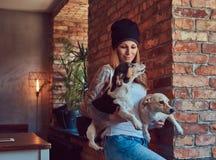 Eine stilvolle tattoed blonde Frau im T-Shirt und in den Jeans hält zwei nette Hunde Lizenzfreies Stockfoto