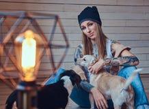 Eine stilvolle tattoed blonde Frau im T-Shirt und in den Jeans sitzt auf einem Bretterboden mit zwei netten Hunden Lizenzfreie Stockfotografie