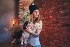 Eine stilvolle tattoed blonde Frau im T-Shirt und in den Jeans umfasst zwei nette Hunde Stockbilder
