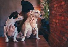 Eine stilvolle tattoed blonde Frau im T-Shirt und in den Jeans umfasst zwei nette Hunde Lizenzfreie Stockbilder