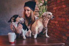 Eine stilvolle tattoed blonde Frau im T-Shirt und in den Jeans umfasst zwei nette Hunde Lizenzfreie Stockfotografie