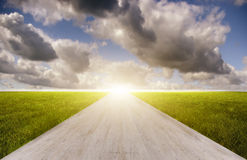Eine Straße zwischen der Wiese mit beweglichen Wolken stockfotografie