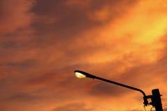 Eine Straßenlaterne gegen den Sonneneinstellungshintergrund Lizenzfreies Stockfoto