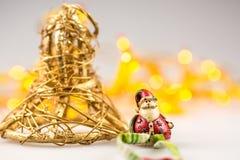 Eine Strohweihnachtsglocke und oneceramic Weihnachtsmann Lizenzfreie Stockfotografie