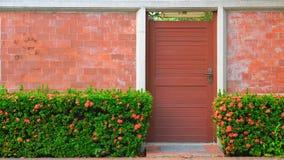 Eine Tür und der Zaun des roten Backsteins mit roten Blumen Stockbilder