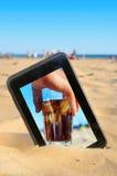 eine Tablette auf dem Sand eines Strandes mit einem Bild eines Mannes mit einem g Lizenzfreie Stockfotografie