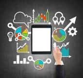 Eine Tablette, digitales Gerät mit Kopienraumschirm wird durch gezogene bunte Geschäftsikonen umgeben Eine Hand zeichnet ein Flus Lizenzfreie Stockbilder