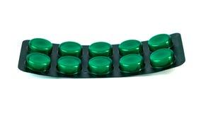 Eine Tablette in einer grünen Blisterpackung, lokalisiert auf einem weißen Hintergrund Stockfotografie