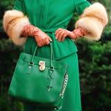 Eine Tasche in den Händen einer Frau Das Mädchen in einem modischen Mantel Nahaufnahme stockfotografie