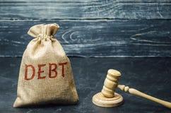 Eine Tasche des Geldes und der Wort Schuld und der Hammer des Richters Zahlung von Steuern und der Schuld zum Zustand Konzept von lizenzfreies stockbild
