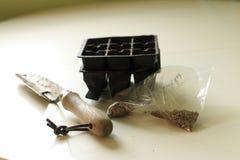 Eine Tasche von Samen nahe bei einer kleinen Schaufel und Modulen f?r das Samenbeginnen Gartenarbeitkonzept- und Fr?hlingss?enkon lizenzfreies stockfoto