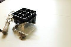 Eine Tasche von Samen nahe bei einer kleinen Schaufel und Modulen f?r das Samenbeginnen Gartenarbeitkonzept- und Fr?hlingss?enkon stockbild