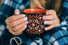 Eine Tasse Kaffee-Orange in den Händen lizenzfreie stockfotos