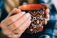 Eine Tasse Kaffee-Orange in den Händen des Mädchens lizenzfreie stockbilder
