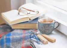 Eine Tasse Tee, eine Decke, alte Bücher und Gläser auf dem Fensterbrett Stockfotografie