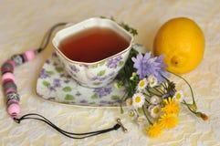Eine Tasse Tee die, des Sommers gelben und blauen Feldblumen, einer Zitrone und einer Halskette auf einer eleganten Spitze tauche Stockbild