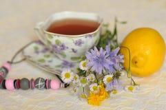 Eine Tasse Tee die, des Sommers gelben und blauen Feldblumen, einer Zitrone und einer Halskette auf einer eleganten Spitze tauche Lizenzfreies Stockbild