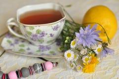Eine Tasse Tee die, des Sommers gelben und blauen Feldblumen, einer Zitrone und einer Halskette auf einer eleganten Spitze tauche Lizenzfreies Stockfoto