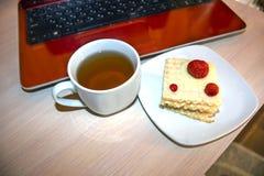 Eine Tasse Tee, ein Stück einer Oblatentorte mit Erdbeeren, ein Laptop Stockfotos