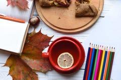 Eine Tasse Tee, einen Apfelkuchen, bunte Blätter, ein offenes Notizbuch, eine Zeichnung und einen Satz von Stockfotos
