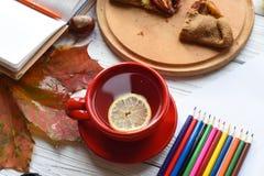 Eine Tasse Tee, einen Apfelkuchen, bunte Blätter, ein offenes Notizbuch, eine Zeichnung und einen Satz von Lizenzfreies Stockbild