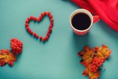 Eine Tasse Tee im Herbstlaub und in der Eberesche Stockfoto