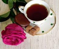 Eine Tasse Tee ist auf dem Tisch, nahe bei der Untertasse sind Bonbons und Plätzchen Rose nahe bei einer Tasse Tee Stockfotos