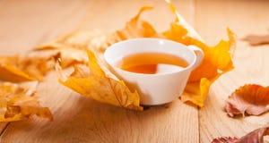 Eine Tasse Tee mit fallendem Herbstlaub des Ahorns, auf dem Hintergrund der hölzernen Tabelle Stockbild