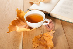 Eine Tasse Tee mit fallendem Herbstlaub des Ahorns auf dem Hintergrund der hölzernen Tabelle Stockbild