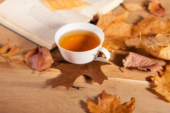 Eine Tasse Tee mit fallendem Herbstlaub des Ahorns auf dem Hintergrund der hölzernen Tabelle Lizenzfreie Stockbilder