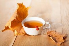 Eine Tasse Tee mit fallendem Herbstlaub des Ahorns auf dem Hintergrund der hölzernen Tabelle Lizenzfreie Stockfotos