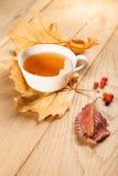 Eine Tasse Tee mit fallendem Herbstlaub des Ahorns und Beeren der Eberesche auf dem Hintergrund der hölzernen Tabelle Stockbilder