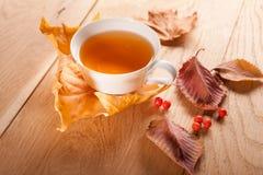 Eine Tasse Tee mit fallendem Herbstlaub des Ahorns und Beeren der Eberesche auf dem Hintergrund der hölzernen Tabelle Lizenzfreies Stockfoto