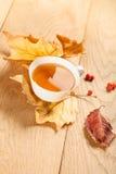 Eine Tasse Tee mit fallendem Herbstlaub des Ahorns und Beeren der Eberesche auf dem Hintergrund der hölzernen Tabelle Stockfoto