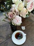 Eine Tasse Tee mit herrlichem Blumenstrauß von frischen Rosen auf dem Tisch im Garten lizenzfreies stockfoto