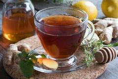 Eine Tasse Tee mit Ingwer, Zitrone, Kräutern und Honig lizenzfreies stockfoto