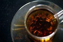 Eine Tasse Tee mit Marmoren auf einer schwarzen Tabelle Stockbilder