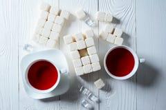 Eine Tasse Tee mit Turm von den Stücken raffiniertem Zucker Lizenzfreies Stockfoto