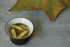 Eine Tasse Tee, eine Schale Blumentee, im grauen Hintergrund! Lizenzfreies Stockbild