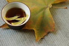Eine Tasse Tee, eine Schale Blumentee, im grauen Hintergrund! Stockbild