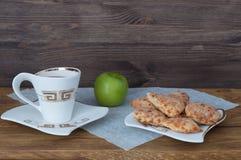 Eine Tasse Tee, selbst gemachte Plätzchen und einen Apfel auf einem Hintergrund von hölzernen Brettern stockbilder