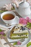 Eine Tasse Tee, eine Teekanne und ein Stück des Spinatskuchens auf einer Tabelle in den hellen Farben im Retrostil stockfotos